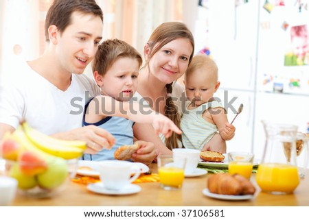 Young happy family with two kids having breakfast together