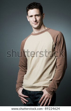 Young happy fashion model posing on gray background. - stock photo