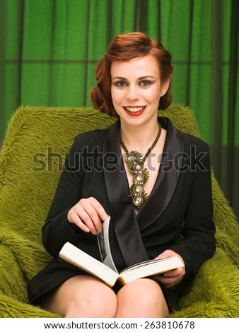 young happy fashionable woman relaxing on furry armchair and reading a book - stock photo
