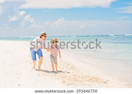 Young happy father and his little son enjoing summer time walking barefoot at the beach with ocean, beautiful clouds on background. Having fun with the kid in summer coast on holidays