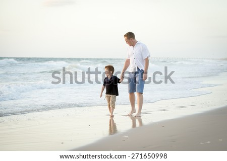 young happy father holding hand of little son walking together on the beach with barefoot in sand in front of sea waves, the kid smiling and having fun with dad in Summer coast holidays - stock photo