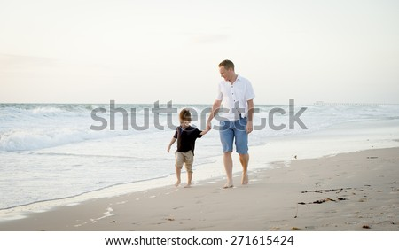 young happy father holding holding hand of little son walking together on the beach with barefoot in sand in front of sea waves, the kid smiling and having fun with dad in Summer coast holidays - stock photo
