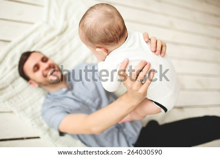 Young happy father holding son in hands lying on rustic wooden floor - stock photo