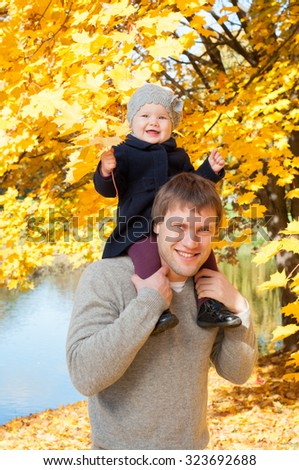 Young happy father with daughter in autumn park - stock photo
