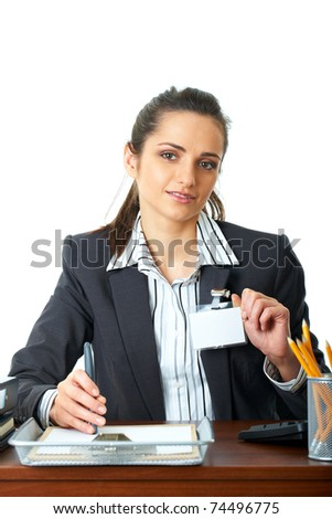 young happy female office worker sits at her desk, holds her id badge, isolated on white background