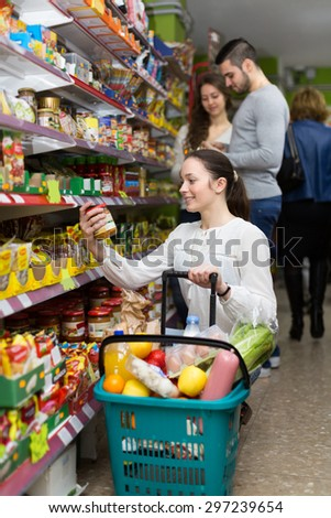 Young happy female purchasing food for week at supermarket - stock photo