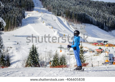 Young happy female skier against ski slopes and ski-lift on background. Woman is wearing helmet skiing glasses gloves and blue ski suit. Winter sports concept. Carpathian Mountains, Bukovel, Ukraine - stock photo