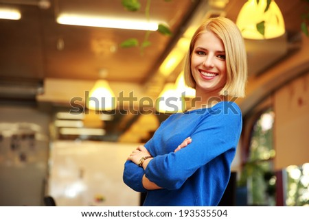 Young happy female student with arms folded standing in campus - stock photo