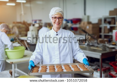 Young happy female worker in sterile cloths holding freshly baked cookies on tinplate inside food production factory.