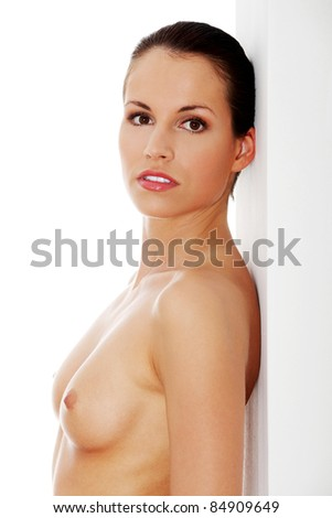 Young, happy, fit, naked woman standing next to white wall - stock photo