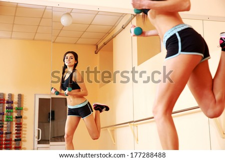 Young happy fit woman doing exercises with dumbells and looking on her reflection in mirror at gym - stock photo