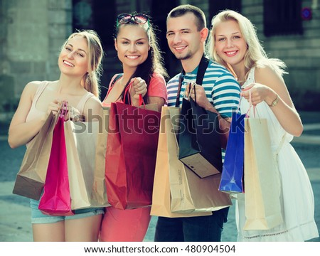 Young happy four people holding many shopping paper bags in town