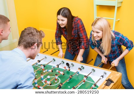 Young happy friends absorbedly playing table hockey two girls against two boys in a yellow room while boys smiling selective focus - stock photo