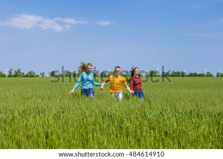 Young happy Friends running on green wheat field. One guy and two girls are jumping, having fun.