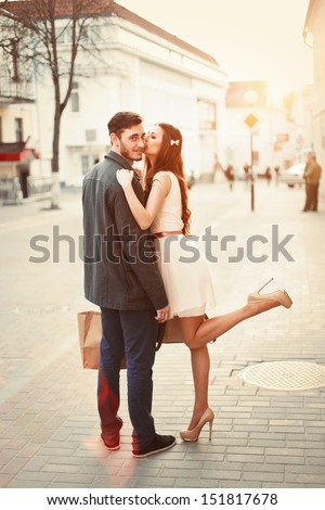 Young happy funny couple lovely posing and kissing outdoor. Handsome man have a gift for his girlfriend. Summer or autumn outdoor portrait.  - stock photo