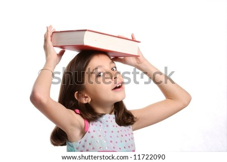 young happy girl / child balancing book on her head - against white background