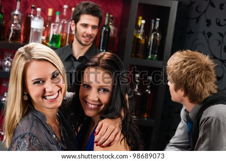 Young happy girl friends at cocktail bar hugging together