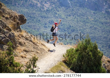 Young happy girl  high jumping in the mountains