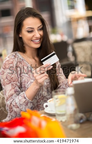Young happy girl holding credit card and shopping online