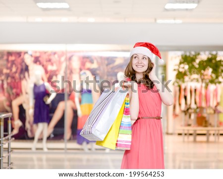 Young happy girl in christmas hat with shopping bags In shopping mall