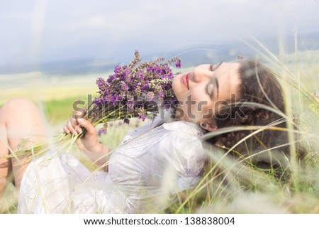 young happy girl in daisy field with colorful flower - stock photo