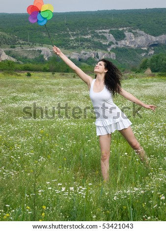 young happy girl in daisy field with colorful flower