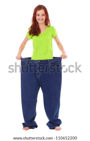 Young happy girl in her old huge jeans, diet concept, isolated on white - stock photo