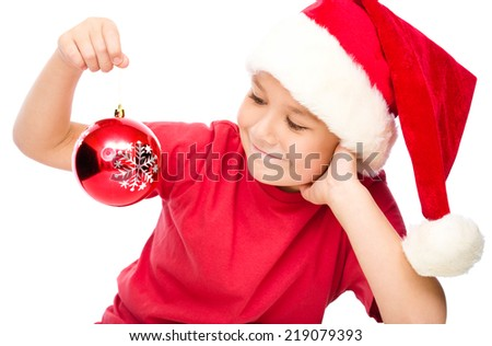 Young happy girl in santa hat is holding a christmas decoration, isolated over white
