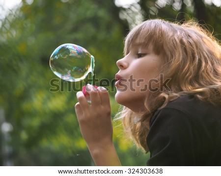 Young happy girl in the park and soap bubbles