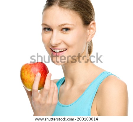 Young happy girl is holding red apple, isolated over white - stock photo