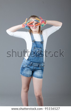 young happy girl.  little girl on a gray background. beautiful little girl with her hands in the paint - stock photo
