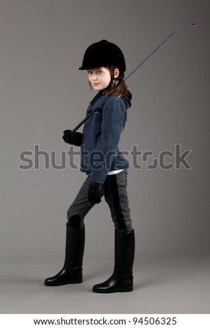 young happy girl.  little girl on a gray background. Horse and jockey - little girl. - stock photo