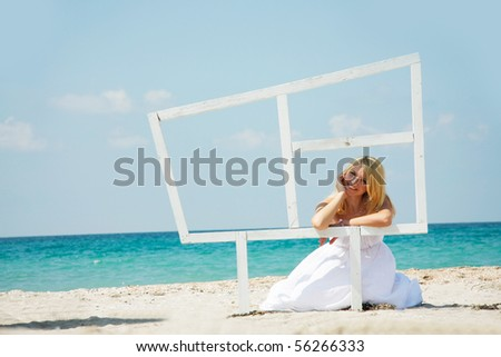 young happy girl looking through wooden window on sea background