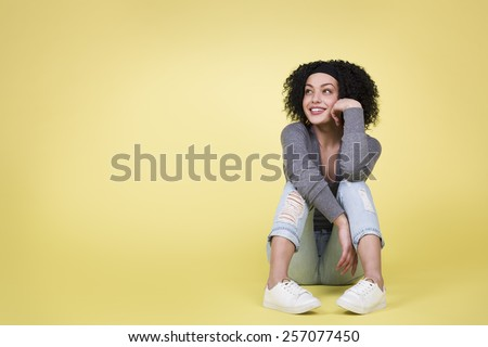 Young happy girl looking up and daydreaming on isolated yellow background with copy space. - stock photo