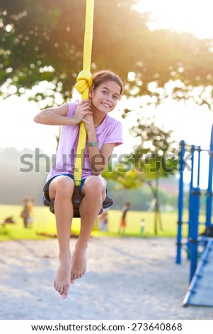 Young happy girl playing on the swing in the park at evening time - stock photo