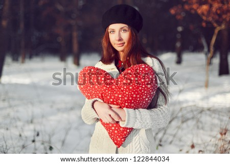 Young happy girl posing in park holding in hands big red heart. - stock photo