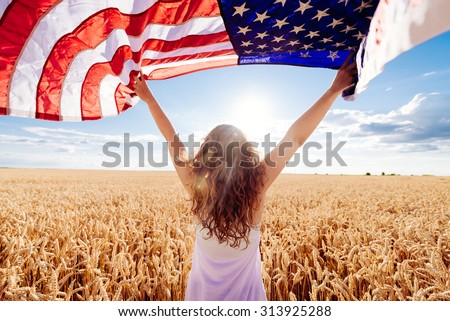Young happy girl running and jumping carefree with open arms over wheat field. Holding USA flag. Toned image. Selective focus. - stock photo
