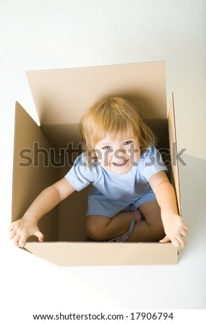 Young happy girl sitting in cardboard box. She's looking at camera. High angle view.