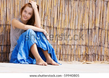 young happy girl sitting near bamboo wall - stock photo