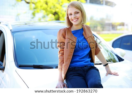 Young happy girl sitting on the hood of a car  - stock photo