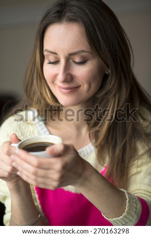 Young happy girl smiling and holding a cup of hot coffee or tea sits in a cafe, lifestyle, breakfast or dinner to spend time relaxing, healthy lifestyle, fashion, in a yellow sweater.