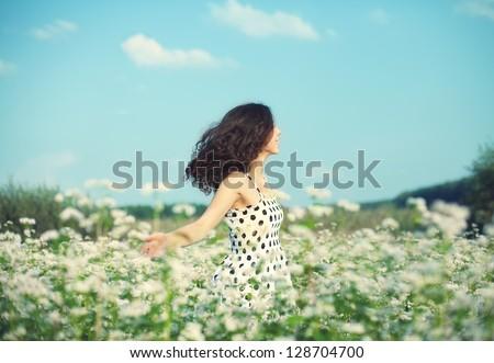 Young happy girl walking on the buckwheat field - stock photo