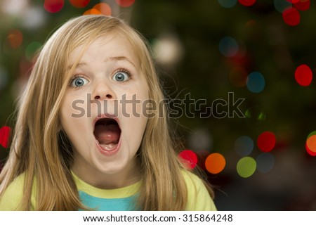 Young happy girl with a surprised look on her face during christmas time - stock photo