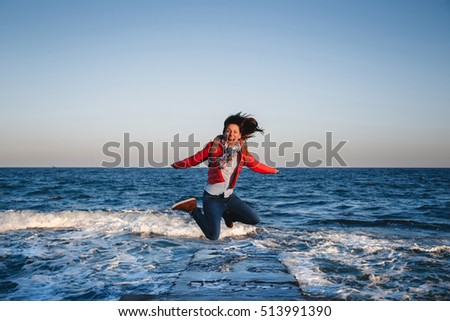 Young happy girl with backpack jumping on a seaside at sunset