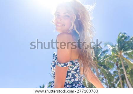 young happy girl with flower bouquet on tropical sea and beach background, smiling happy girl outdoor portrait - stock photo