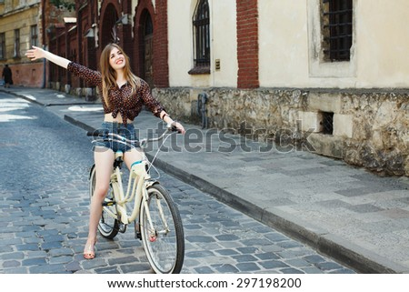 Young happy girl with long blond hair wearing on dark blouse and blue shorts is riding on a bicycle, on the street of old European city  - stock photo