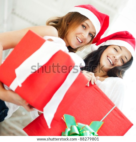 Young happy girls in Christmas hats.Standing together indoors and holding big gift boxes