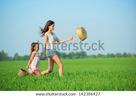 Young happy girls running with basket at green wheat field with her friend together