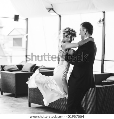 young happy groom holding hands to his beloved wife - stock photo