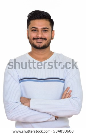 Young happy handsome Indian man with arms crossed